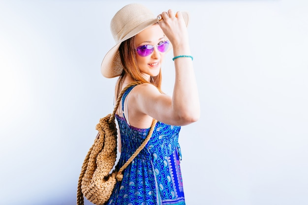 Bella giovane donna adulta con cappello, abito da spiaggia e occhiali estivi viola si voltò guardando dritto davanti a sé. concetto di vacanza estiva su sfondo bianco