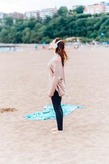 Bella giovane donna adulta che ascolta musica sulla spiaggia in una nuvolosa giornata estiva o primaverile indossando le cuffie