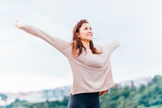 Bella giovane donna adulta con le braccia aperte che sorride con la sensazione di libertà
