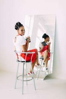 Il bello giovane insieme afroamericano della tenuta della donna dell'estetista di compone le spazzole e la sorveglianza nello specchio