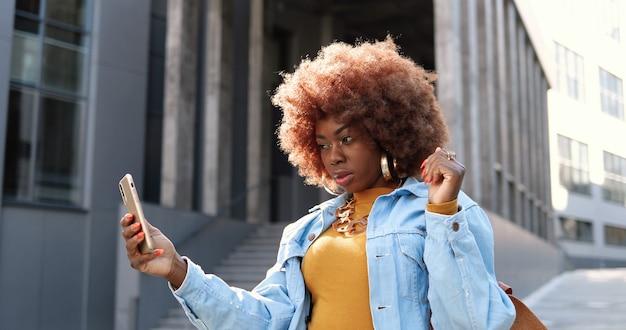 Bella giovane donna riccia afroamericana in posa per la fotocamera dello smartphone mentre si prende la foto di selfie in strada. femmina fredda abbastanza elegante che fa le foto dei selfie con il telefono cellulare.