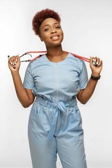 Bello giovane medico o infermiere afroamericano con lo stetoscopio che sorride isolato su white