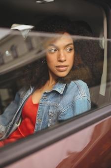 Bella giovane donna afroamericana autista dai capelli neri in giacca di jeans seduto in una nuova auto marrone