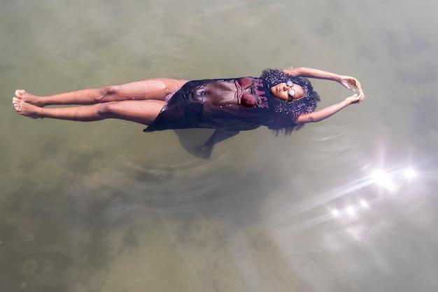 Bella giovane donna afroamericana che galleggia in una pozza d'acqua
