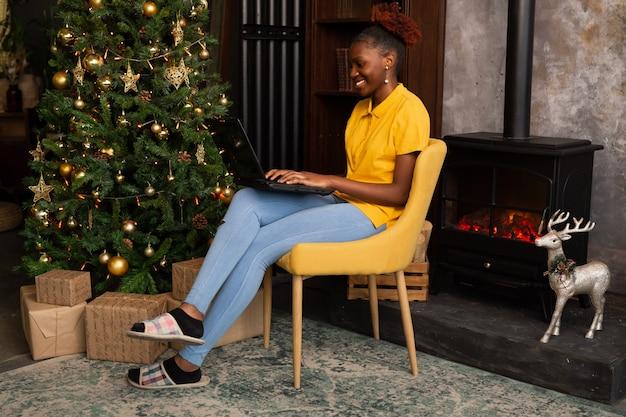 Bella giovane donna africana seduta con il computer portatile al chiuso vicino all'albero di natale