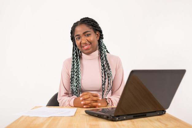 Bella giovane femmina africana al tavolo con il portatile