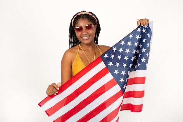 Bella giovane femmina africana su sfondo bianco che indossa occhiali da sole con la bandiera americana