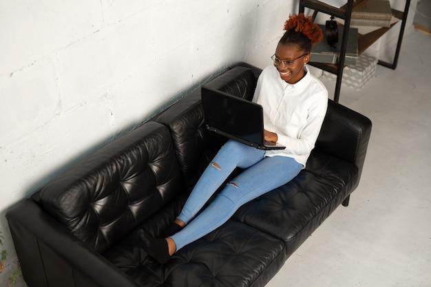 Bella giovane femmina africana in una camicia bianca con un computer portatile si siede su un divano nero