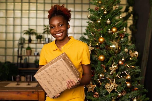 Bella giovane femmina africana con un regalo vicino all'albero di natale