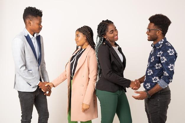 Belle giovani africani su sfondo bianco si stringono la mano