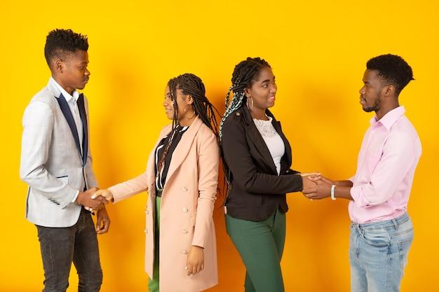 Belle giovani africani su uno sfondo giallo si stringono la mano
