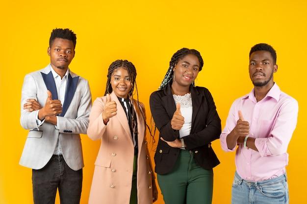 Belle giovani africani su sfondo giallo con gesto della mano