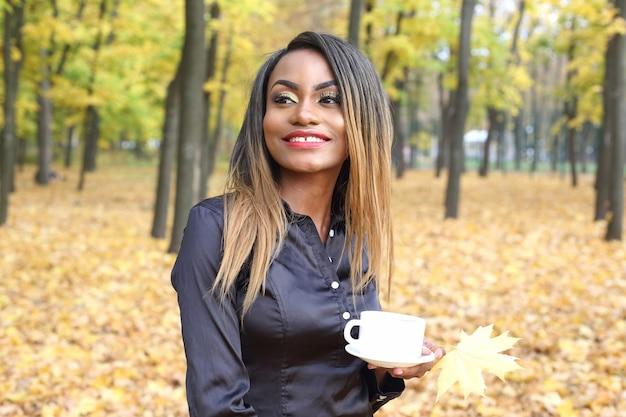Bella giovane donna africana che beve caffè da una tazza bianca sullo sfondo di foglie di autunno nel parco