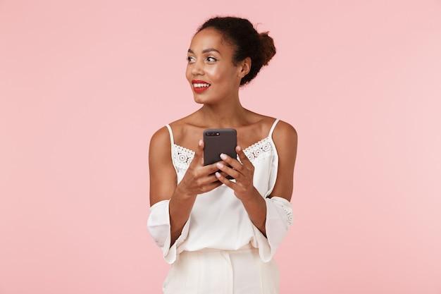Bella giovane donna africana isolata sopra la parete rosa del backgroung facendo uso del telefono cellulare
