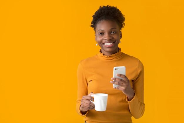 Bella giovane donna africana con un telefono e una tazza