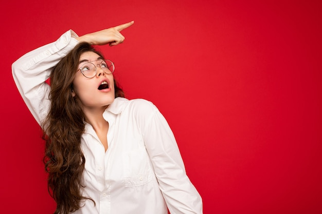 Bella giovane stupita scioccata e stupita donna bruna riccia che indossa una camicia bianca e occhiali da vista