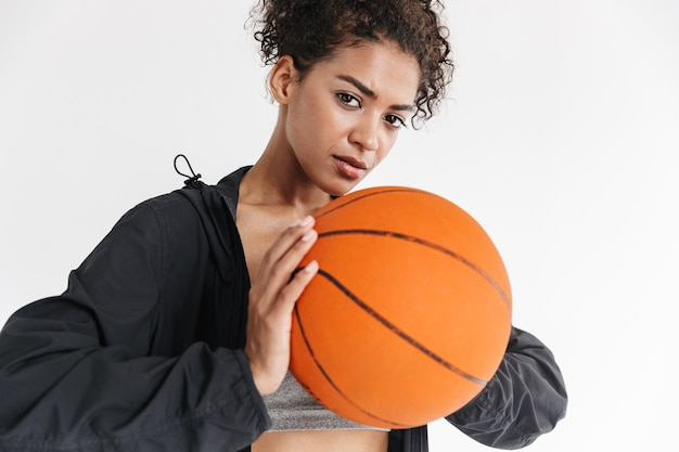 Bella giovane donna africana incredibile fitness sportivo in posa con il basket.