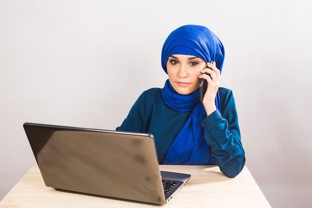 Bella giovane donna araba parlando al cellulare su bianco