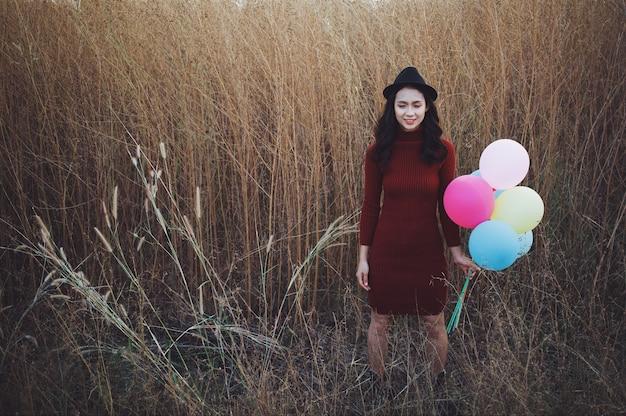 La bella giovane ragazza asiatica tiene i palloncini al bellissimo campo