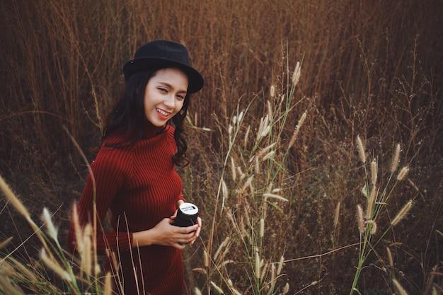 La bella giovane ragazza asiatica tiene il caffè al bellissimo campo
