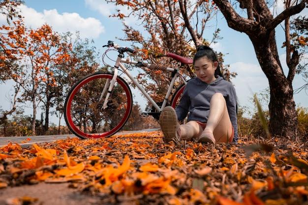 Bella giovane donna asiatica che si siede accanto alla sua bici all'aperto all'albero di palash con la priorità bassa piena del bello fiore arancione