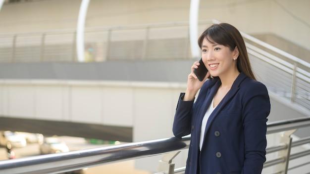 La bella giovane donna asiatica di affari sta usando lo smartphone nella città moderna