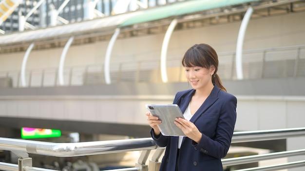 La bella giovane donna asiatica di affari sta usando la compressa nella città moderna