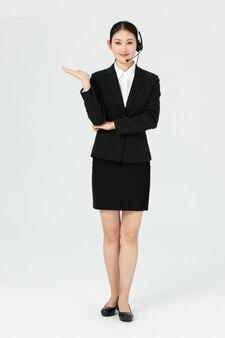 Bella giovane donna asiatica di affari con la cuffia per call center
