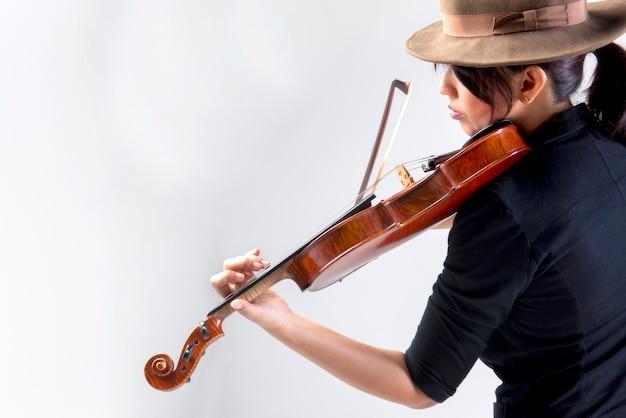Bella giovane donna asiatica elegante che suona il violino nella musica classica