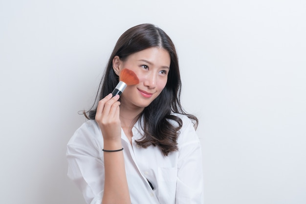 Bello giovane modello femminile asiatico che mette arrossire con il pennello cosmetico in camicia bianca