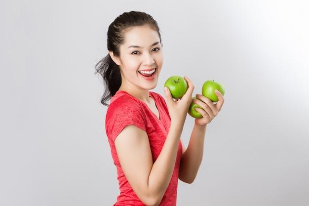Il sorriso felice della bella giovane donna asiatica di forma fisica tiene la mela verde.