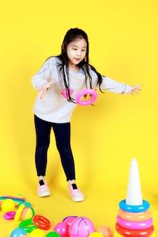 La bella giovane ragazza asiatica si diverte a lanciare un cerchio colorato nel cono triangolare per sfidare l'abilità del controllo degli oggetti per accumulare un cerchio di plastica sul terreno della scuola di un giocattolo divertente e una palla per far giocare i bambini