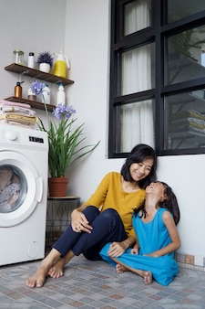 Bella giovane madre asiatica e figlia che aspettano la lavatrice della lavanderia per finire la filatura