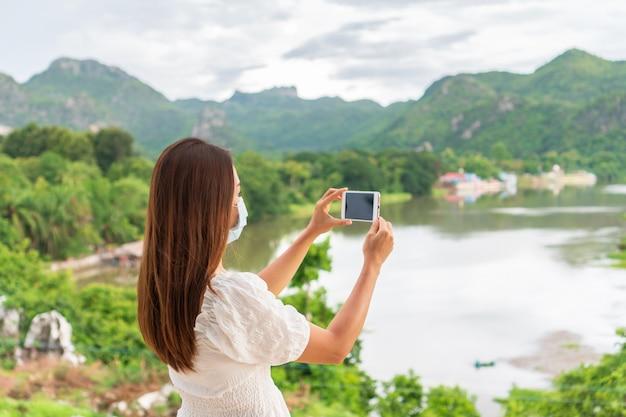Bella giovane donna asiatica del viaggiatore che indossa una maschera protettiva in un luogo pubblico a causa della riduzione della diffusione del 19, nuovo stile di vita normale, concetto di viaggio