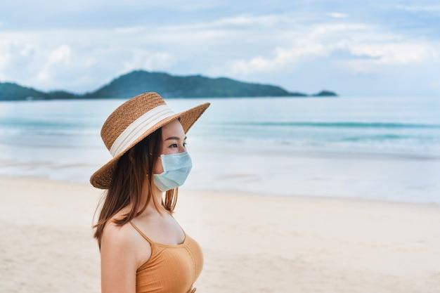 Bella giovane donna asiatica viaggiatore con maschera protettiva in spiaggia.