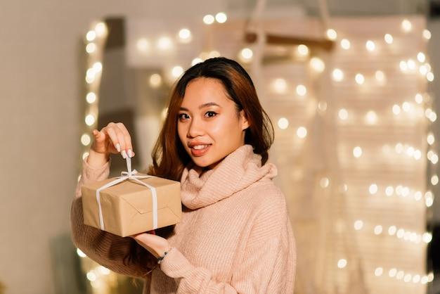 Bella giovane donna asiatica che celebra il natale a casa, divertendosi mentre apre i regali