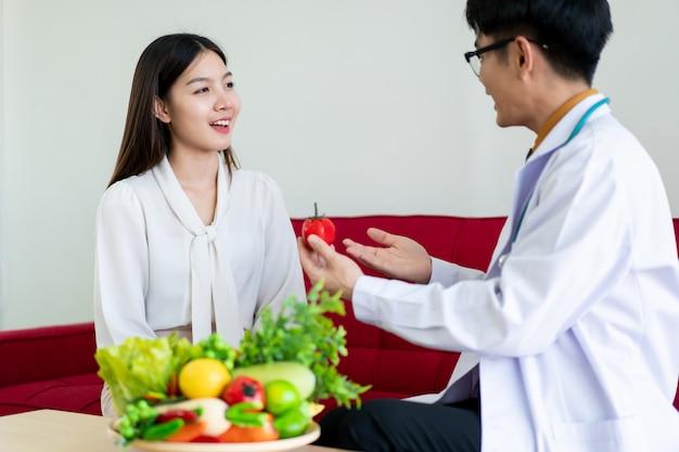 La bella giovane donna asiatica viene a incontrare il nutrizionista in ospedale e a parlare di dieta e alimentazione salutare. medico che spiega sull'assistenza sanitaria al paziente. benessere e concetto di consumo di salute.