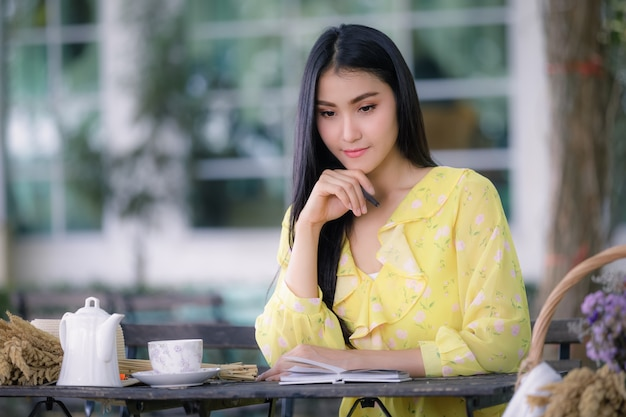 La mano della bella giovane donna asiatica sta scrivendo sul blocco note con una penna in giardino e una tazza di tè con il fiore sul tavolo