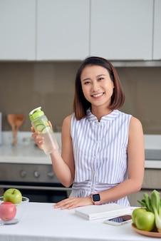Bella giovane donna asiatica che tiene bevanda disintossicante in cucina. bevanda sana, concetto di cibo per la perdita di peso.