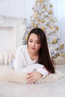 Bella giovane donna asiatica in soggiorno decorato con albero di natale