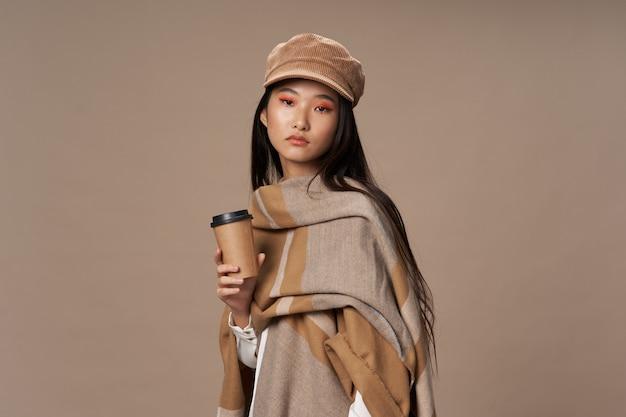 Bella giovane donna asiatica che propone in vestiti alla moda di inverno