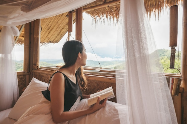 Bella giovane donna asiatica che riposa e legge un libro sul letto in una capanna con il tetto di paglia tra la montagna in vacanza