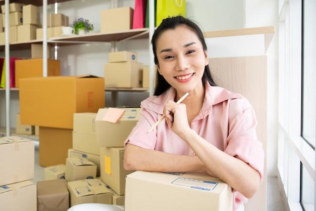 Bella giovane donna asiatica che vende prodotti attraverso il mercato online