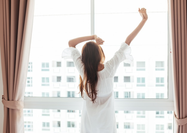 Bella giovane donna asiatica che si siede sul letto e che si estende al mattino in camera da letto.
