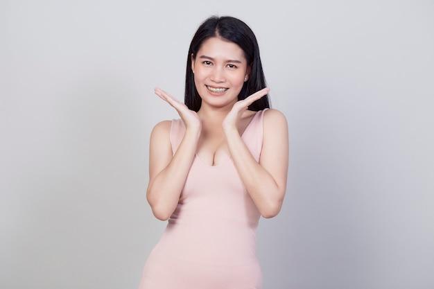 Il ritratto sorridente della bella giovane donna asiatica una ragazza con l'abito rosa di usura ha un divertimento e felice di positivo con successo isolato su fondo bianco