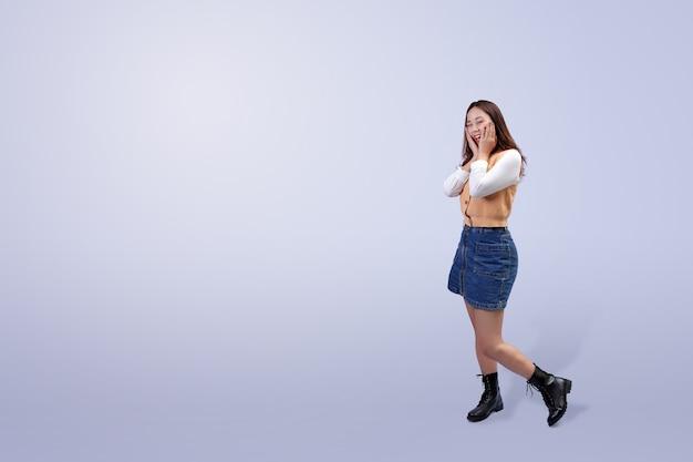 Bella giovane donna asiatica in piedi e sorridente con la mano che tocca il viso