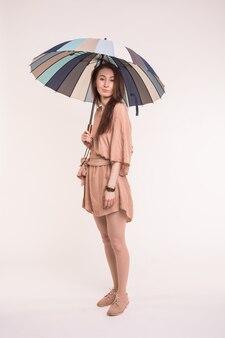 Bella giovane donna asiatica che sta sotto l'ombrello a strisce in vestito grazioso sulla parete bianca.