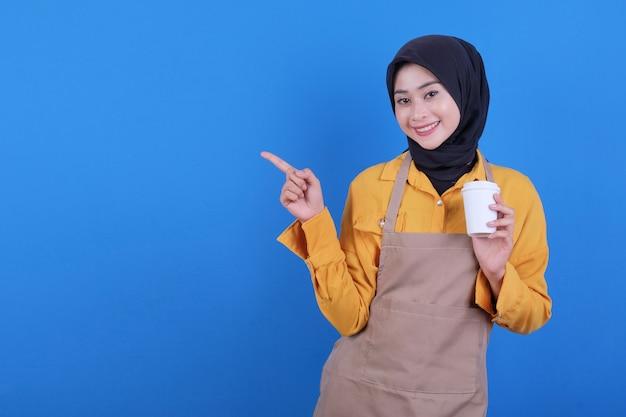 La bella giovane donna asiatica indossa il grembiule che tiene un bicchiere di caffè e che indica il lato sinistro
