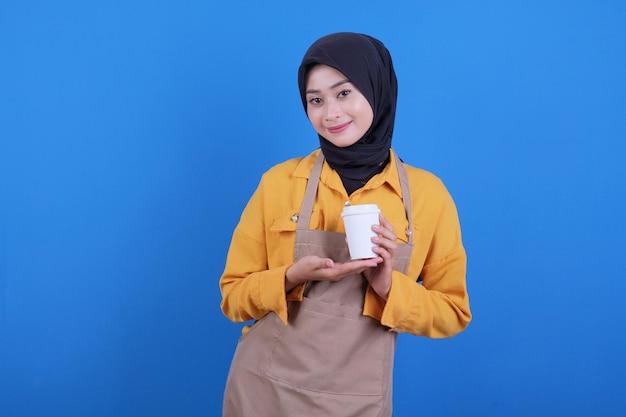 La bella giovane donna asiatica indossa il grembiule che tiene un bicchiere di caffè