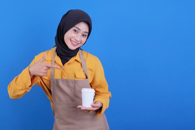 La bella giovane donna asiatica indossa il grembiule che tiene e indicandole un bicchiere di caffè
